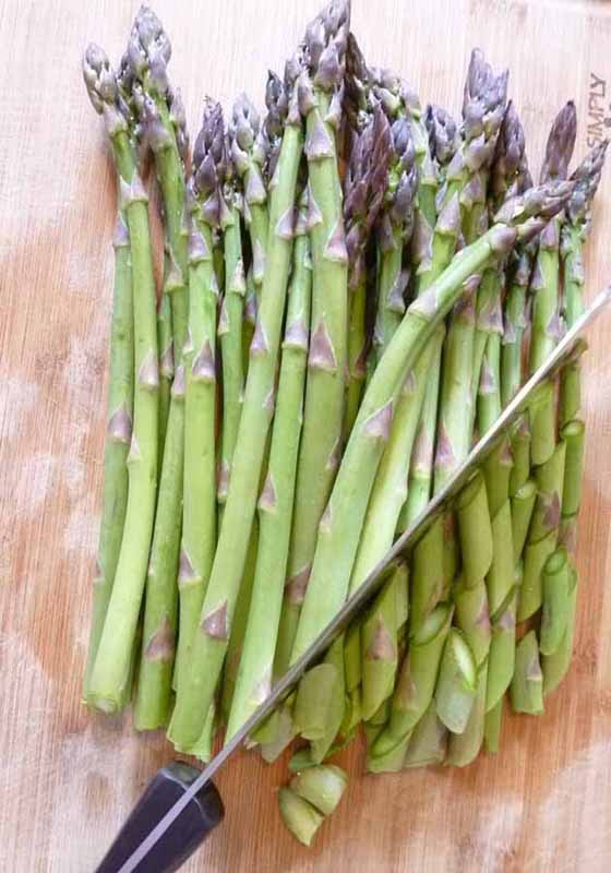 Cutting raw asparagus on a bias